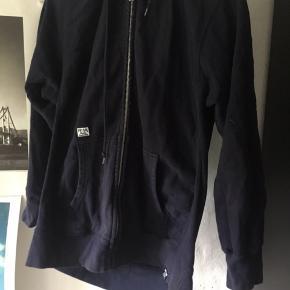 Flot hoodie, i fed blå farve med neongult logo på ryggen.