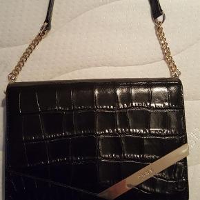 """Varetype: HELT NY taske Størrelse: Alm. Farve: Sort Oprindelig købspris: 1800 kr.  Den smukkeste taske fra DKNY.  Aldrig brugt. Inde i tasken er der et stort rum og en stiklomme+lynlåslomme. Bagpå en stiklomme. Aftagelig/justerbar skulderrem med guld hardware. Krokopræget kalvelæder. Under tasken er der ligeledes 4 guld """"dutter"""" Jeg bytter ikke..😊"""