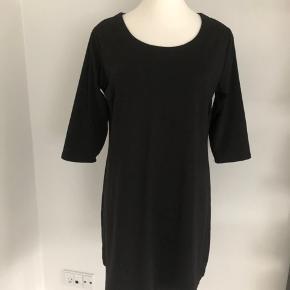 Tidsløs og enkel sort kjole fra ZNK med 3/4 lange ærmer.  Lukkes med lynlås på ryggen.  Længde fra skulder er 92 cm, brystmålet er 116 cm, og taljen måler 110 cm.  Fremstillet af 80% polyester, 13% viscose og 3% elastan.  Bærer ikke præg af brug.