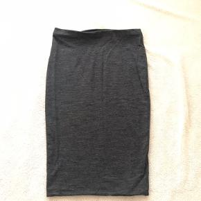 Nederdelen er stram. Længden er til knæene