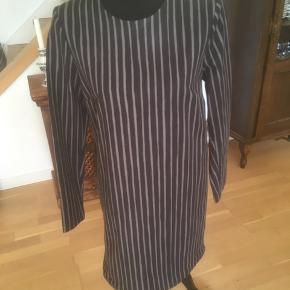 Så gin sort kjole med grå striber på langs. Kjolen er lagt op. Gennemforet med sort polyesterfoer. Vaskemærket i siden er fjernet. Materialet er bomuld. Brystmål er 94 cm Længde er 85 cm Skjult lynlås i ryggen.