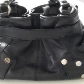 """Varetype: Håndtaske Størrelse: Mellem Farve: Sort Oprindelig købspris: 2800 kr. Fed taske den ligger ml """"God men brugt"""" og """"Som næsten ny""""  37 cm. bred. 14 cm. dyb. 18 cm i højden. Dustbag medfølger.  NEDSAT MED 83 %"""