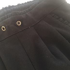 Suit-agtige bukser i sort med flæsedetaljer ved hoften og lommerne. Stumper ved anklerne. Elastikken i taljen mangler, men der kan sættes en ny i, og ellers kan de også sagtens bruges uden🌼🌼