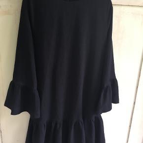 Klassisk sort kjole fra Ganni i str s/36. Længde 58 cm, brystmål 2x49 cm. Den er lavet af polyester/elastane. Den er god men brugt og har lidt vaskefnuller deraf prisen. Bytter ikke, sælges for 450 kr. Se også mine andre annoncer!!!