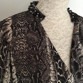 Skjorte med slange print. V hals og perler på krave og ærmer. Polyester. Længde 75. Bryst 112. Så den kan også passes af en XL.   Kig forbi mine annoncer 😊 Altid god mængderabat