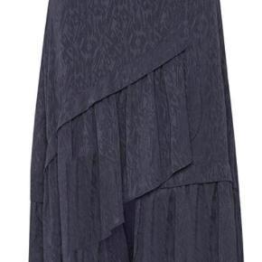 Varetype: Nederdel Farve: Mørke blå Oprindelig købspris: 999 kr.  Nederdelen er aldrig brugt, jeg har købt den for en måned siden men har fortrudt.                                 Beskrivelse: Nederdel med et asymmetrisk snit og brede flæsekanter foran. Skjult lynlås i siden.                                 100% polyester