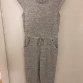 Sød grå buksedragt med korte ærmer købt i H&M der er trykknaplukning i nakken, elastik i taljen og 2 lommer foran. Ingen huller/pletter. Ved forsendelse betaler køber fragtomk.