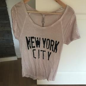 Palliet bluseSød t-shirt i flot rosa farve med pailletter på ærmerne.. Aldrig brugt ( mærke stadig på ) Nypris 250,-