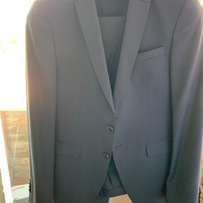 Flot, navyblåt jakkesæt (inklusiv vest) fra Hugo Boss. Brugt 3 gange. Fremstår som nyt, pånær lille fold i knæhasen. Aldrig lagt op.  NP: 4700 kr