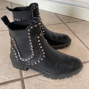 Grove støvler med nitter (sølv) og elastik i siden. Detaljer med 'slangeskind'. Rund snude.  Alm i str. Lidt brugsspor i form af ridser. Bagpå den ene sidder en enkelt nitte lidt løs.  Byd