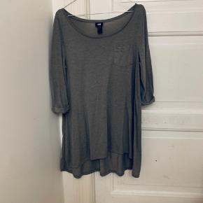Grå lang bluse. Jeg har brugt den som kjole. Den er lidt kortere fortil end bagtil