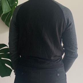 Lækker Mads Nørgaard strik med sort front og bag og grå ærmer.  Kvalitet: 50% merino uld, 50% akryl