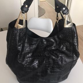Den fede DKNY shopper i slangeskinds-look. Med gulddetaljer og lommer samt lynlåsrum. Standen er god men brugt. DKNY Mærke og guldspænder (se billede) har brugsmærker.