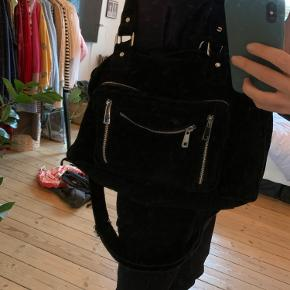 """Fed rummelig crossbody taske i sort ruskind fra nunoo. Modellen hedder """"Mille"""" og måler. 14x23x40 cm. 🌸 Tasken har desuden også skulder stropper, og kan bruges på begge møder. Foret i det lille rum foran er sluppet en smule, men det betyder ikke noget for brugen af rummet. Derfor er standen sat """"god men brugt"""", resten af tasken er i rigtig fin stand."""