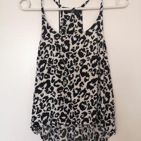 Top str 36 i sort/hvid leopard print. Kortere foran end bagpå, god til at 'tucke' ind i højtaljede bukser/nederdel 😊