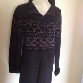 Lang strikket cardigan. 100%uld. Kun brugt en enkelt gang, er som ny. Hel længde fra skulder: 84 cm. Kan også fint bruges af en str. L