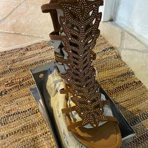 Nok sommerens fedeste sandal. Total skinnende. Får masser af opmærksomhed. Sandalen er blød og med super lækker komfort. Farven er tan. Nye og ubrugte.