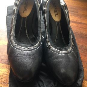 Chanel sko sorte med lille hæl og logo på hælen ,der er lidt slid på hælen ellers meget fin stand str. 41   700 Kr.