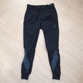 Bukser fra Adidas i str. 34.  Måler ca. 70 cm i omkreds. Og måler ca. 73 cm i længden, målt fra indersømmen på buksebenet.  Der er slitage omkring snorene (se sidste billede).  Hentes i Roskilde eller sender med DAO mod betaling af fragt.