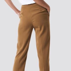 Fine karamel-farvede bukser fra NA-KD  Aldrig brugt og købt til omkring 360kr Strørrelse medium