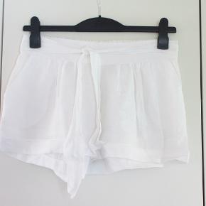 Italienske:  Shorts m bindebælte Størrelse: M/L  Lækre shorts med elastik i linningen bagpå og med bindebælte. Materialet er 95 % bomuld + 5 % elastan.   Livvidde: 40 - max 50 cm x 2 (pga elastik bag på linningen) Længde: 30 cm  Bytter ikke, og prisen er fast