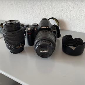 """Varetype: Nikon D3000 Størrelse: - Farve: Sort Oprindelig købspris: 5000 kr.  Nikon, D3000 + ekstra linse (se nedenfor)  Medfølger: - Lang lader + batteri - Ekstra linse, 55-200mm. - Memory card  OBS: Den linse som oprindeligt følger med kameraet har fået et """"hak"""" (se billede). Dette har dog ikke betyder noget for billederne eller billedkvaliteten.  Byd gerne!"""