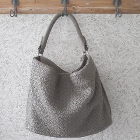 Helt ny og meget smuk taske i skind. Der følger også en lang strop med i samme farve og selvfølgelig dustbag. Den har et stort forrum med magnetlukning og to rum indvendigt. Tasken er lavet af blødt skind.  Mål: B: 30 cm. L: 42 cm. D: 13 cm. Alle mål er ca. da det er svært at være præcis.   Nypris 1800,- kr.