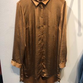Fin skjortebluse i blød, tung kvalitet med god længde og slidser i siderne. Er lidt længere bagtil. Skjorten er størrelsessvarende.  Aldrig brugt, kun vasket.  BYTTER IKKE!