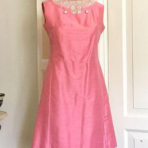 Brand: Vintage Varetype: 60'er-kjole Farve: Rosa  Smuk og elegant 60'erkjole i silke. Med broderet chiffon og pynteknapper i halsen. Lynlås bagpå og foret. Str 38. Bryst 95cm. Liv 81cm.  Se også mine mange andre sager. Jeg giver gerne mængderabat. Så sparer du også på portoen.