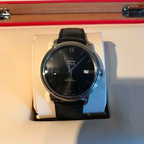 Jeg sælger mit Omega-ur, da det bliver brugt for lidt. Uret er fra 2016, hvorfor der er længe til service. Al tilbehør medfølger, og uret er i pæn stand. Remmen er en smule slidt, hvilket ses af billederne. Ægtheden af uret har endvidere været tjekket hos Klitgaard i Aalborg, hvor uret også blev registeret på Watch-Matters.com  Uret befinder sig i Aalborg, og der kan forekomme afslag i prisen ved hurtig handel :-).  Model: 424.13.40.20.01.001 Producenter: Omega Serie: De Ville Prestige Co-Axial 39.5mm Type: Herreur, dress Diameter: Ø 39.5 mm Tykkelse: 10 mm Urkasse: Stål Bagkasse: Solid Armbånd: Sort læder Urskive: Sort med romertal og indeksmarkeringer Spænde:Remspænde i stål Glas: Ridsefast safirglas Bezel (krans): Stål Urværk, type:Automatisk, selvoptrækkende Sekundvisere: Flydende Urværk: Omega 2500 (baseret på ETA 2892-A2) med 27 juveler, 25200 vph Gangreserve:48 timer Type af dato: Dato Vandbeskyttelse: 3 ATM  Yderligere info: Kronometer certifikat (COSC)