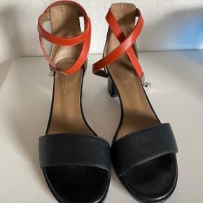 Smuk Hermes Manege sandal i sort kalveskind med orange wrap ankel strap, brugt 1 gang i ca 1 time, købt lidt for små. Insål længde 23,3 cm, hælhøjde 5 cm. Kommer med box, kvittering og skoposer.