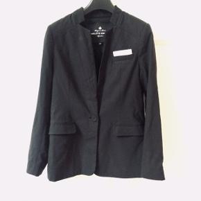 En klassisk sort blazer med twist. Fint lille fastsyet lomme-tørklæde og symmestriske syninger der skaber en smuk pasform og fald. Str 36 og rummelig. Den er sort. Sælger med mobilepay og afhentning eller med Dao forsendelse/ herinde.