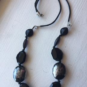 """Elegant retro- halskæde i sort og sølvgrå. """"Stenene"""" er af plastic.  Længde: 70 cm.  Halskæden fremstår som ubrugt."""