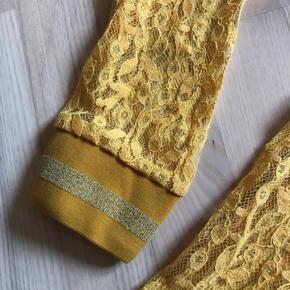 Den smukkeste gennemsigtige blondebluse med fine detaljer på skulderne og ved ærmerne. Str L og alm i str.   Kig gerne mine andre annoncer, giver gode mængderabatter