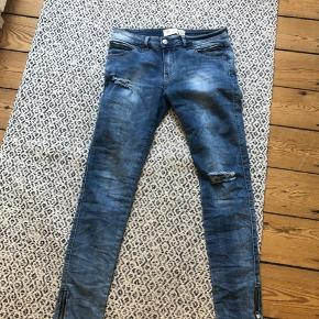 Fede jeans med mange detaljer  Lynlås ved bukseben, slidtage og skjult lynlås ved lomme og 2% strech  Sidder perfekt  Str 40/L Materiale : bomuld , elastan  Aldrig brugt   Sendes med DAO på købers regning