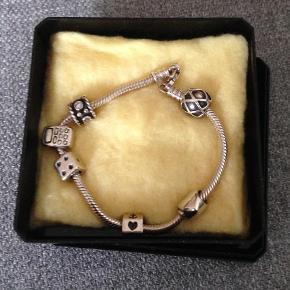 Varetype: Armbånd Størrelse: Ca. 19,5 cm Farve: Sølv Prisen angivet er inklusiv forsendelse.  Sølv Pandora armbånd, seks vedhæng. Brugt men stadig fint.
