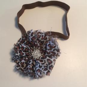Varetype: hårbånd Størrelse: onesize Farve: Brun  Flot hårbånd med roset i leopardstof - kan bruges fra nyfødt.   20,- pp