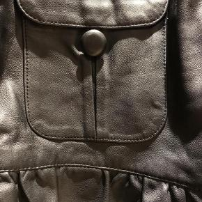 EKSTRA NEDSAT!!! Smart feminin kort skindjakke med flæser og 3/4 ærmer.  Mål:  Bryst ca. 100  Længde ca. 55  Feminin skindjakke - flæser, 3/4 ærmer Farve: Grå Oprindelig købspris: 1400 kr.