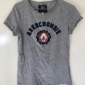 Sælger min Abercrombie & Fitch T-shirt i grå   Bemærk at i kanterne er den rå, sådan er den købt i butikken. Altså ikke brugsspor