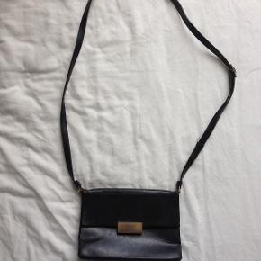 Stella McCartney taske i faux leather. Den er slidt. Læderet har nogle ridser og metallukningen er ridset, som billederne viser. Desuden virker magneterne i lukningen ikke. Bortset fra det, så er der ikke huller eller andre defekter. En fin taske med en del patina.   Bredde: 20 cm Højde: 14 cm Dybde: 6.5 cm