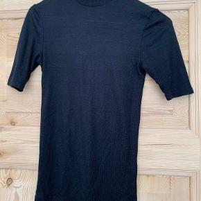"""Sort turtleneck t-shirt fra Envii i str.XS. Den er blevet vasket en del gange og stoffet er derfor lidt """"fnuldret"""", men ellers fejler den ikke noget."""