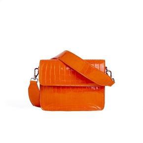 Hvisk Cayman Shiny Strap Bag Orange. Er blevet brugt til et bryllup, men har hængt i skabet lige siden. Sælges fordi jeg ikke får den brugt. Ny pris 499 kr - kom med et bud :)