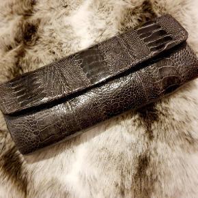 Clutch fra Naledi i sort skind fra strudseben. Måler 25 x 10 cm. Brugt, men stadig pæn. Nypris var 1999,- kvittering haves.