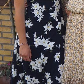 Smuk wrap / slå om kjole i mørkeblå med hvide blomster.