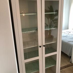 Sælger dette fine vitrineskab. Trænger til at blive genspændt :) Der ligger hyldepapir på nogle af hylderne, men det er lige til at tage af :)