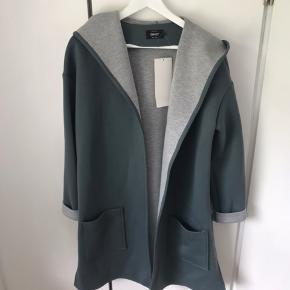 jakke/ cardigan i kraftig Sweatshirt stof med hætte. Købt ny som vareprøve. Støvet grøn farve, med grå inderside.