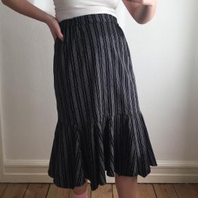 Sort- og hvidstribet nederdel fra Masai. Den er brugt få gange og er i god stand. Det er en størrelse S. Jeg er en størrelse S.