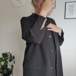 Smuk frakke i tynd kvalitet - perfekt som sommer- eller forårsfrakke. Smuk slids ved begge ærmer og tre tryk-knapper.  Jakken har været brugt få gange til finere arrangementer, og fejler absolut intet.  Lidt lille i str., Svarer måske til en L.