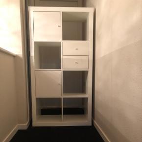 Hvid IKEA reol, slidsspor på hylder men slid ses ikke, når der er bøger på hylderne