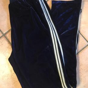 Fede velour bukser i den blødeste kvalitet og smukkeste blå farve. Sort og guld striber ned langs benene. Brugt få gange.